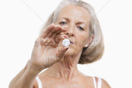 Medication : Portrait of senior woman holding a pill against white background