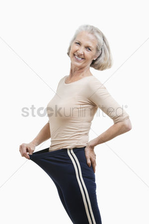 Loss : Portrait of senior woman in oversized pants against white background