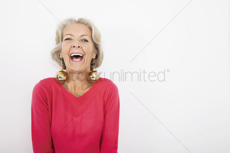 Celebrating : Portrait of senior woman wearing christmas ornaments over white background