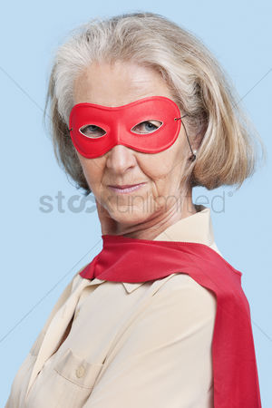 Senior women : Portrait of senior woman wearing superhero costume against blue background