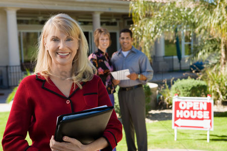 Mature : Portrait of smiling estate agent with house and home buyers in background