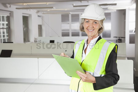 Supervisor : Portrait of smiling senior woman in reflector vest and hard hat holding clipboard at office