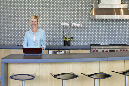 Arts : Portrait of smiling senior woman using laptop in kitchen
