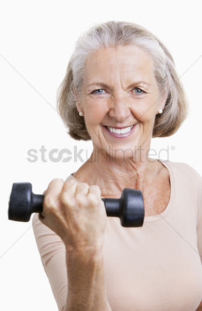 Dumbbell : Portrait of smiling senior woman with dumbbell against white background