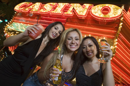 Celebrating : Portrait of three young women toasting in front of illuminated casino las vegas nevada usa