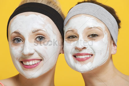 Spa : Portrait of two happy women with face pack on their faces over yellow background