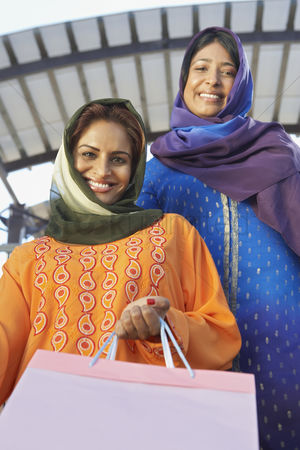 Spending money : Portrait of two muslim women with shopping bags
