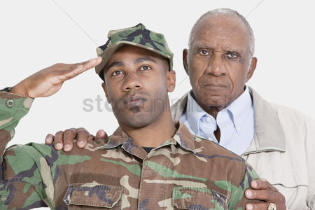 Respect : Portrait of us marine corps soldier with father saluting over gray background