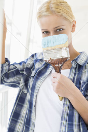 Shyness : Portrait of woman holding paintbrush in front of face