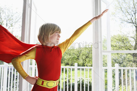 Arm raised : Portrait of young boy  7-9  wearing superhero costume arm raised indoors