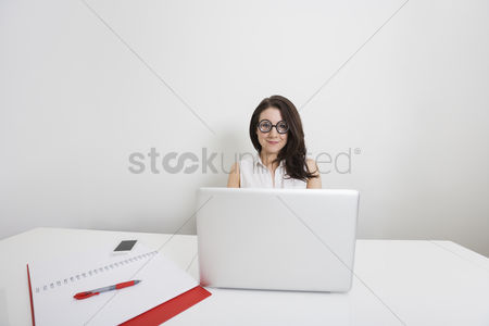 Cell phone : Portrait of young businesswoman in nerd glasses with laptop at desk in office