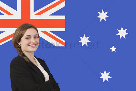 Respect : Portrait of young businesswoman smiling over australian flag