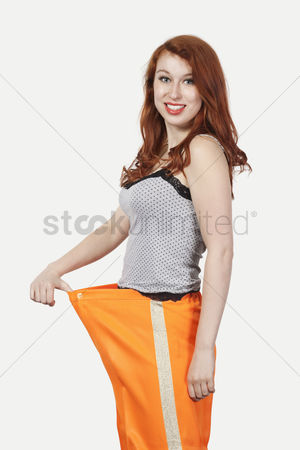 Loss : Portrait of young caucasian woman oversized orange pants against gray background