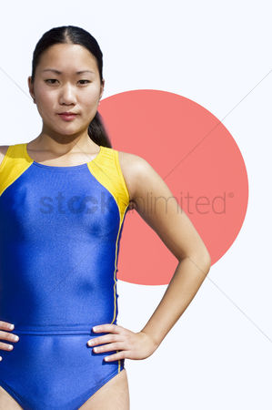 Respect : Portrait of young female athlete standing with hands on hips over japanese flag