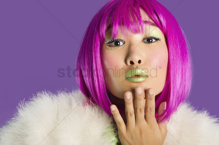Fashion : Portrait of young funky woman in pink wig blowing kiss over purple background
