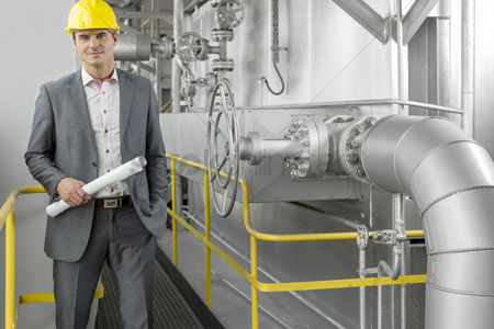 Supervisor : Portrait of young male architect holding blueprint by machinery at industry