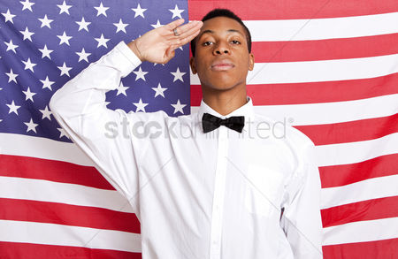 Respect : Portrait of young man saluting against american flag