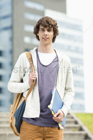 College : Portrait of young man standing at college campus