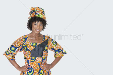 Traditional clothing : Portrait of young woman in african print attire standing with hands on hips over gray background