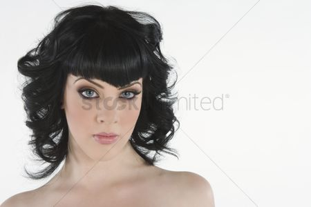 Black background : Portrait of young woman with black hair and blue eyes