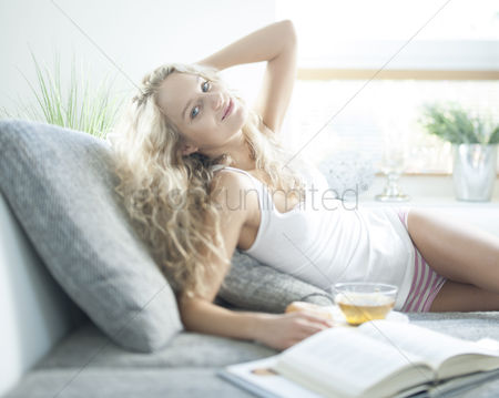 Czech republic : Portrait of young woman with herbal tea relaxing on sofa