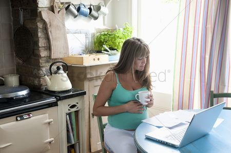 Furniture : Pregnant woman sitting at kitchen table with laptop