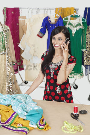 Traditional clothing : Pretty indian female dressmaker answering phone call while standing at table