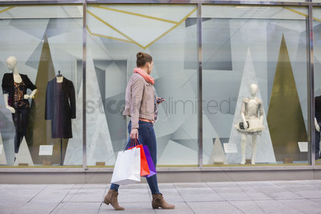 Shopping : Profile shot of young woman with shopping bags looking at window display
