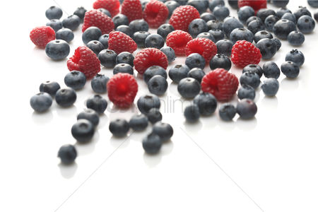 Background : Raspberries and blueberries on white background