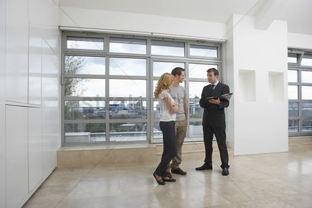 Interior : Real estate agent showing couple new apartment