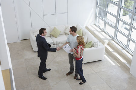Interior : Real estate agent with couple in new home man shaking hand elevated view