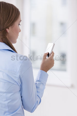 Businesswomen : Rear view of a woman holding a smart phone