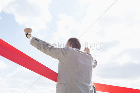 Celebrating : Rear view of businessman crossing finish line against sky