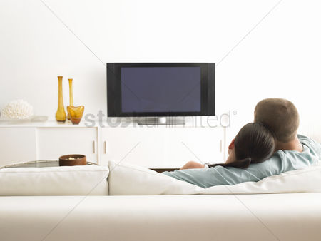 Interior : Rear view of couple on sofa watching tv