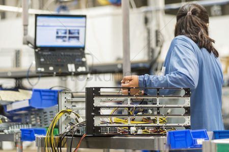 Hispanic : Rear view of female technician repairing computer part in electronics industry