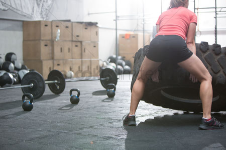 Strong : Rear view of woman flipping tire in crossfit gym