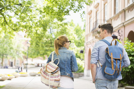 College : Rear view of young college friends talking while walking in campus