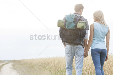 Three quarter length : Rear view of young hiking couple holding hands while walking in countryside