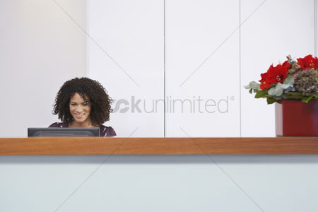 Assistance : Receptionist sitting behind reception desk using computer