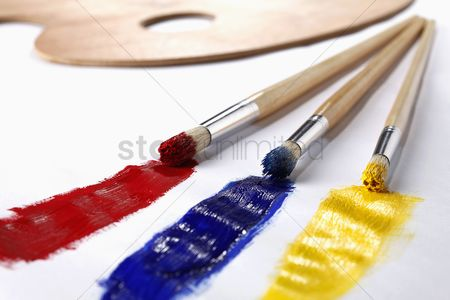 Arts : Red  blue and yellow paint trails from paintbrushes