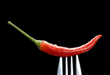 Black background : Red chilli on fork