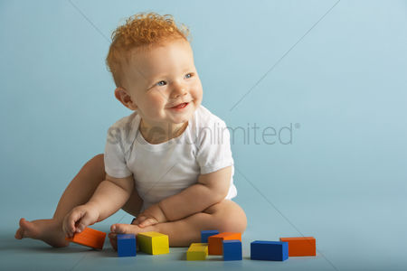 Smiling : Redheaded baby playing with blocks