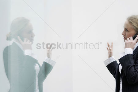 Adulthood : Reflection of a business lady using cell phone