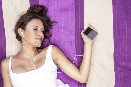 Resting : Relaxed woman listening to music through mp3 player using headphones while lying on picnic blanket