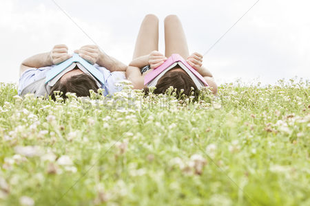 Grass background : Relaxed young couple covering faces with books while lying on grass