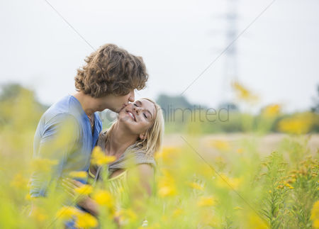 Two people : Romantic man kissing woman in field