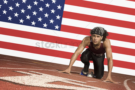 Proud : Runner on a track in starting block in front of us flag