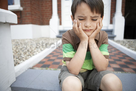Steps : Sad little boy sitting on front steps of house close up