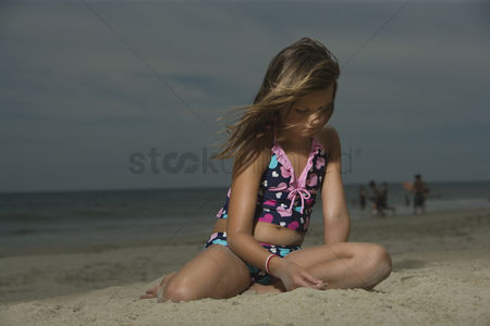 Wondering : Sad little girl sitting on a beach