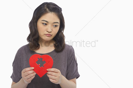 Shape : Sad woman holding up a red heart shape with a missing puzzle piece